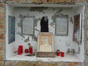 In der Nische unter dem Kreuz werden Kerzen angezündet.